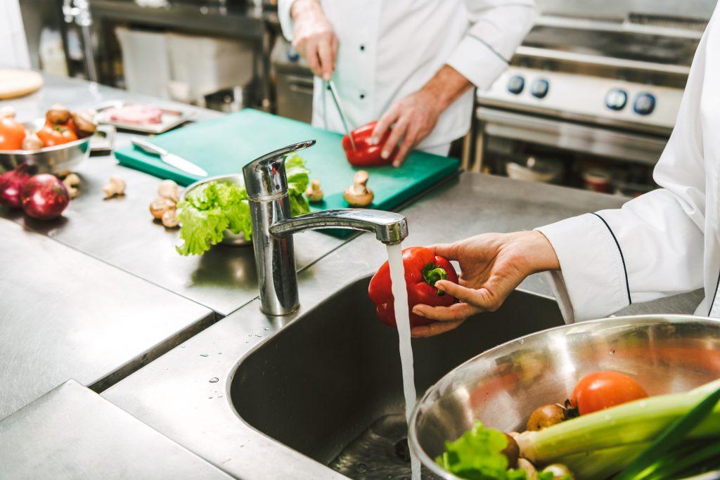Chef preparing food and washing vegetables