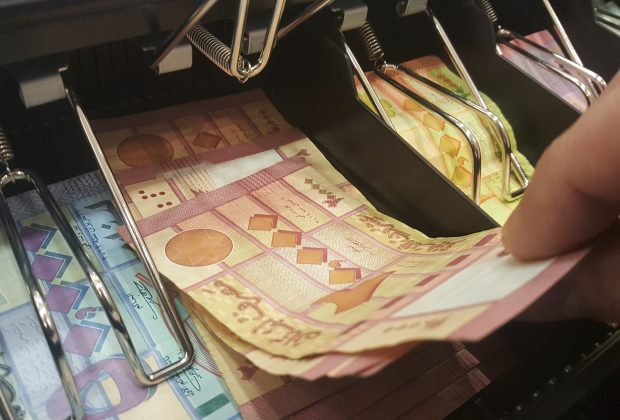 Cashier cashing in lebanese money from cash drawer in a super market