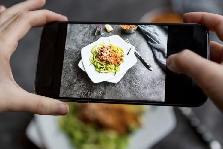 حد المؤثرين في الطعام يلتقط صورة للطعام في مطعم للمراجعة