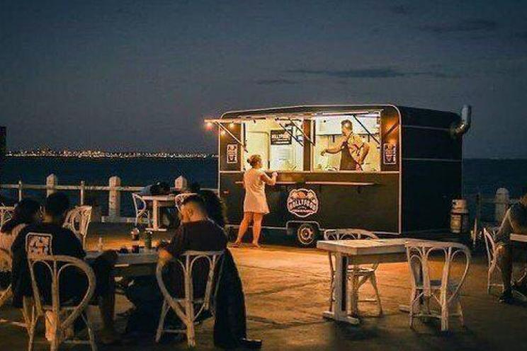 A food truck operating seasonally at night and serving customers food