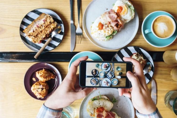 A food influencer is taking pictures from restaurants