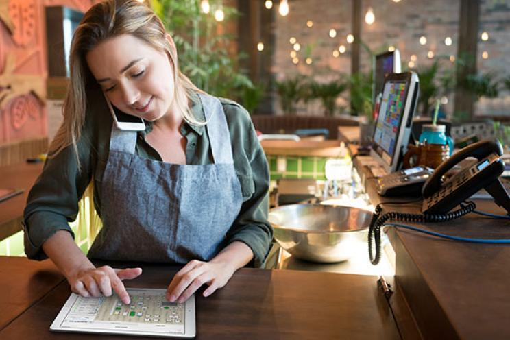 نادلة تستخدم برنامج الحجز لعمل حجز طاولة