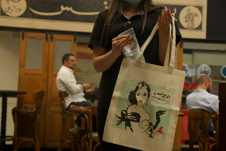 Café Youness tote bag held by a customer