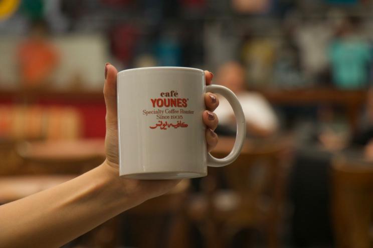 Café Younes branded mug held by a customer