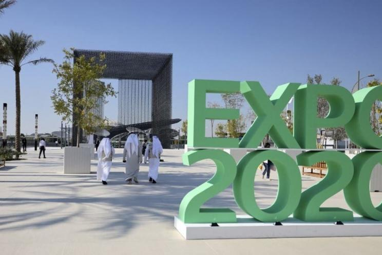 The logo of Dubai Expo 2020 and people from all over the world visiting the exhibition