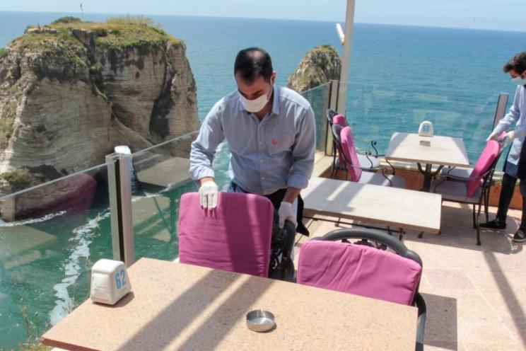 A waiter cleaning a table at a restaurant wearing a mask during the pandemic